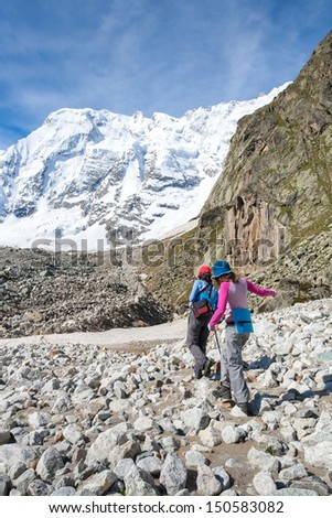 Hikers are approaching wall covered with snow in Caucasus mountains  in Bezengi region, Kabardino-Balkaria, Russia - stock photo