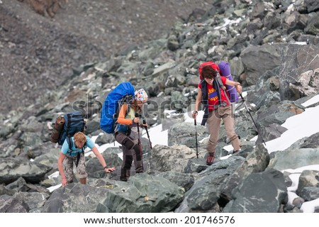 Hikers are climbing rocky slope of mountain in Altai mountains, Russia - stock photo