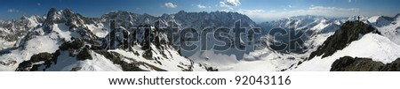 Hikers are going on mountain edge. Panorama of winter High Tatra Mountains. - stock photo