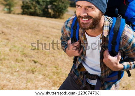 Hikers are the happiest! Close-up of Handsome young man carrying backpack and looking forward a with smile