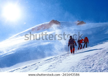 hikers at the top of a pass with backpacks meeting the sunrise in the mountains. Mount Kazbek, Georgia, Caucasus. - stock photo