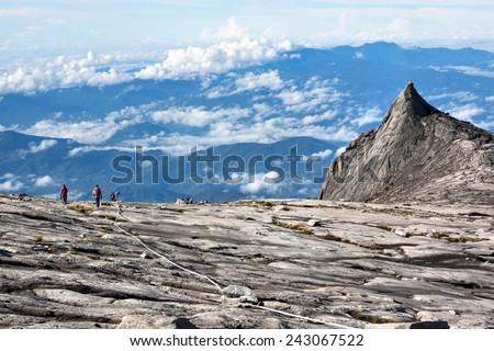 Hikers at the top of Mount Kinabalu in Sabah, Malaysia. - stock photo