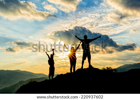 hikers celebrating success on top of a hill in the sunset - stock photo
