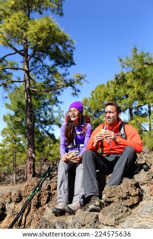 Hikers couple relaxing eating lunch sandwich. Hiking people living active lifestyle in mountain nature. Woman and man hiker sitting during hike on volcano Teide, Tenerife, Canary Islands, Spain. - stock photo