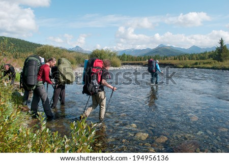 hikers crossing mountain river, Ural, Russia - stock photo