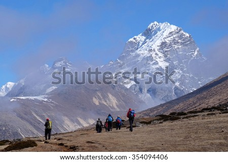 Hikers from Dingboche to Everest Base Camp, with view of Mt Tobuche, Upper Khumbu, Nepal. Sunny morning with mountain fog clearing. - stock photo