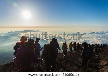 Hikers gather during sunrise on the Mt. Fuji summit .