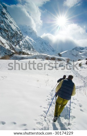 Hikers go up in mountains - stock photo