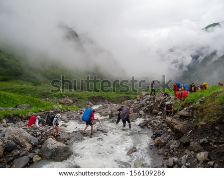 Hikers group cross the mountain river ford - stock photo
