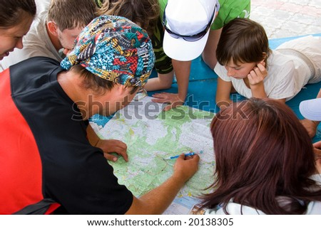 Hikers group planning path on the map - stock photo