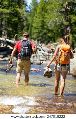 Hikers group walking barefoot crossing river in forest. Adventure people on hike hiking in nature holding shoes and boots to cross with wet feet. - stock photo