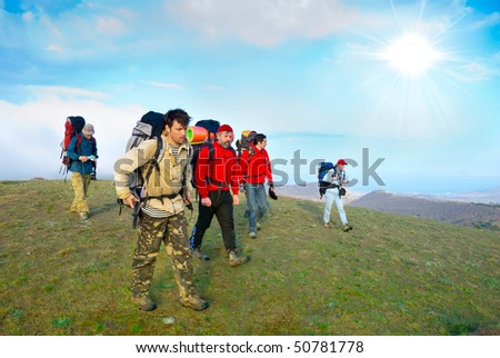 Hikers group walking in spring mountains - stock photo