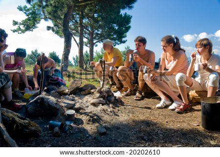 Hikers have breakfast in camp in mountains - stock photo