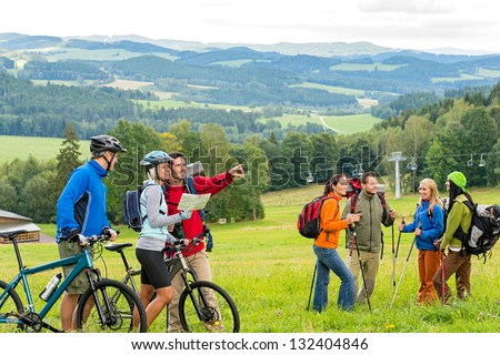 Hikers helping cyclists following track in nature landscape - stock photo