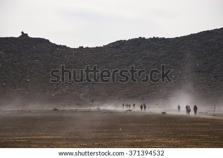 Hikers hiking across the south crater on the Tongariro Crossing - stock photo