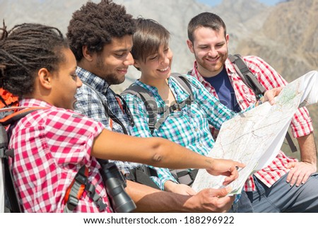 Hikers Looking at Map on top of Mountain - stock photo