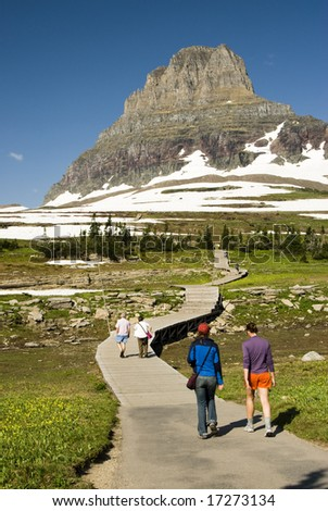 hikers on Hidden Lake Trail in Glacier National Park - stock photo