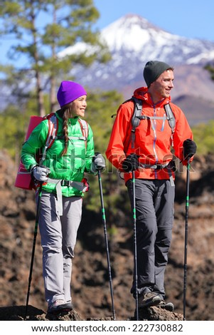 Hikers people hiking - healthy active lifestyle. Hiker couple hiking in beautiful mountain nature landscape. Woman and man hikers walking during hike on volcano Teide, Tenerife, Canary Islands, Spain. - stock photo