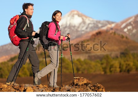 Hikers people hiking - healthy active lifestyle. Hiker people hiking in beautiful mountain nature landscape. Woman and man hikers walking during hike on volcano Teide, Tenerife, Canary Islands, Spain. - stock photo