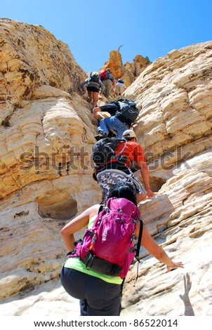 hikers scrambling up rock wall - stock photo