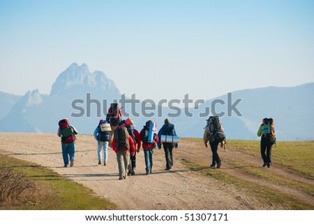 Hikers walk along the rocky footpath - stock photo