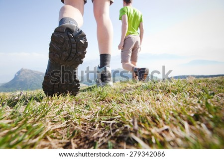 hikers walking in the mountains, close up of the foot, low angle - stock photo