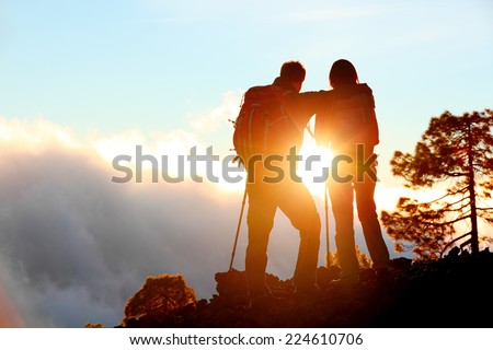 Hiking adventure healthy outdoors people standing talking. Couple enjoying sunset view above the clouds on trek. Video of young woman and man in nature wearing hiking backpacks and sticks. - stock photo