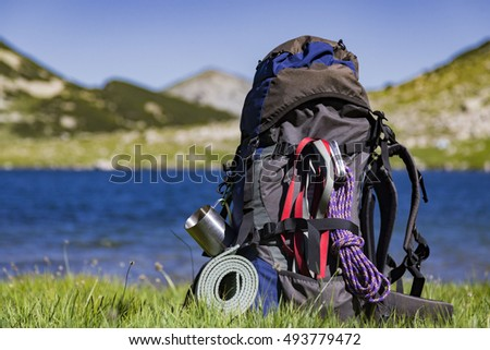 Hiking backpack camping and mountain exploring tourist equipment outdoor on grunge wall. Adventure, summer, tourism active lifestyle