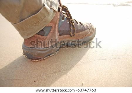 hiking boot in sand beach - stock photo