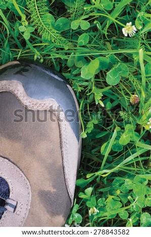 Hiking boot off-road shoe wet green summer grass clover pattern detail vertical textured macro closeup, copy space background, ecological footprint concept earth resource consumption ecology metaphor - stock photo