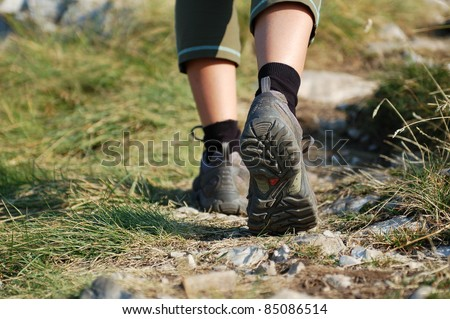 Hiking Boots/Hiking Boots and Legs of a Woman on the Mountain Path - stock photo