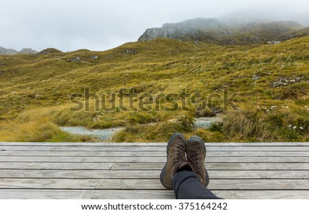 hiking boots on wood board with alpine view in New Zealand - stock photo