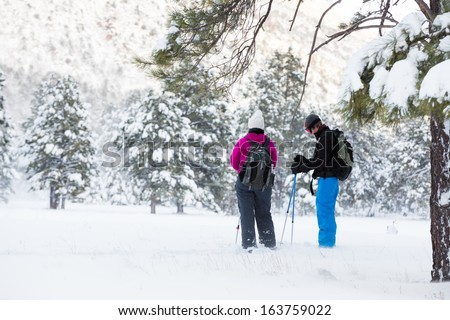 Hiking Break (Couple hiking in snowshoes take a break under a tree) - stock photo