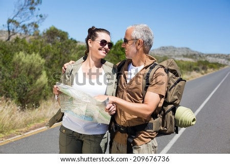 Hiking couple looking at map on the road on a sunny day - stock photo