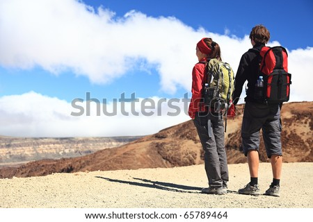 Hiking couple looking at the view holding hands in Teide National Park, Tenerife -  Copy space. Image from the volcano on the hiking path to Montana Blanca. - stock photo