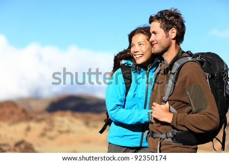 Hiking couple looking at view smiling happy. Young beautiful multiracial couple hikers in their twenties on hike. - stock photo