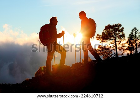 Hiking couple looking enjoying sunset view on hike during trek in mountain nature landscape at sunset. Active healthy couple doing outdoor activities. - stock photo