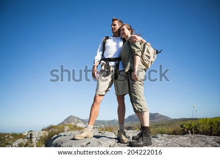 Hiking couple looking out over mountain terrain on a sunny day