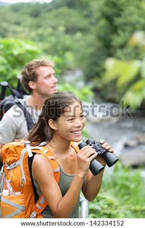 Hiking couple of hikers in outdoor activity wearing backpacks. Woman hiker looking with binoculars smiling happy. Healthy lifestyle image from Iao Valley State Park, Wailuku, Maui, Hawaii, USA. - stock photo