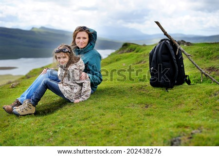 Hiking family adventure on mountain trek: beauty kid girl and her  active mother in jackets and special boots having rest on green lawn with mountain lake view: Scotland, Skye - stock photo