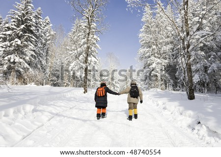 Hiking in snowy forest - stock photo