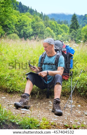 Hiking in the Carpathian mountains. Hiker checks the directions with a map and navigator sitting on the forest meadow