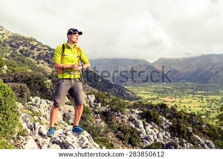Hiking man checking direction in mountains. Hiker trekking in inspirational beautiful landscape looking at view and gps watch, sport smart watch. Healthy lifestyle outdoors concept. - stock photo