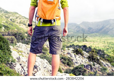 Hiking man looking at beautiful mountains view inspirational landscape. Hiker trekking with backpack on rocky trail footpath. Healthy fitness lifestyle outdoors concept, Crete Greece - stock photo