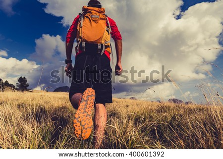 Hiking man or trail runner walking in inspirational mountains landscape. Travel in Italy, Europe. Fitness and healthy lifestyle outdoors in fall autumn nature. - stock photo