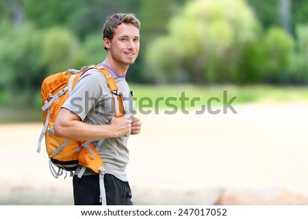 Hiking man portrait with backpack walking in nature. Caucasian man smiling happy with forest in background during summer trip in Yosemite National Park, California, USA. - stock photo