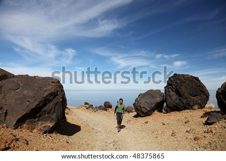 Hiking on Teide Tenerife. Man backpacking on Montana Blanca within the national park of Teide on Tenerife amoung the black Teide eggs or in spanish: Los Huevos del Teide. Blue sky for copy space. - stock photo