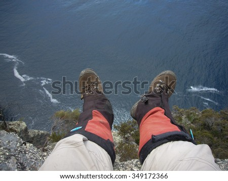 Hiking over the cliff abyss feet in boots high over the ocean not falling