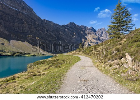 Hiking path along mountain lake in front of swiss mountains, green grass hills and blue sky, Switzerland, Truebsee near Engelberg - stock photo
