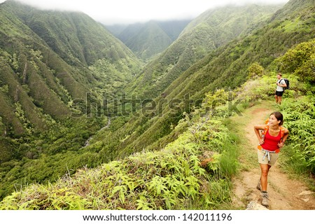 Hiking people on Hawaii, Waihee ridge trail, Maui, USA. Young woman and man hikers walking in beautiful lush Hawaiian forest nature landscape in mountains. Asian woman hiker in foreground. - stock photo